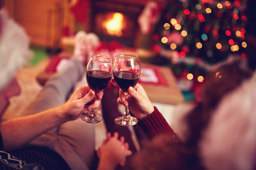 romantic couple with red wine, against xmas tree and fireplace